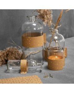 Nahkapaperilla koristellut lasipullot ja tuikkulasi