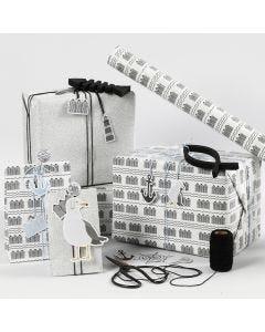 Mustan, valkoisen ja hopean värisiä lahjapaketteja etiketeillä, puisilla kaloilla ja ravistettavilla paperiliittimillä