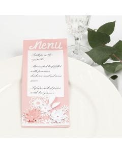 Pitsikartongilla ja kukilla koristeltu menu