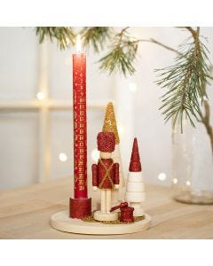 Pähkinänsärkijällä, joulukuusilla ja lasihelmillä koristeltu kynttilänpidike