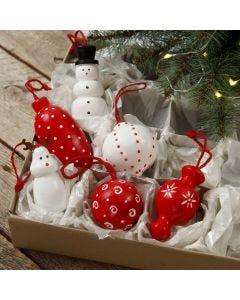 Askartelumaalilla koristeltuja puisia hahmoja ja joulupalloja.
