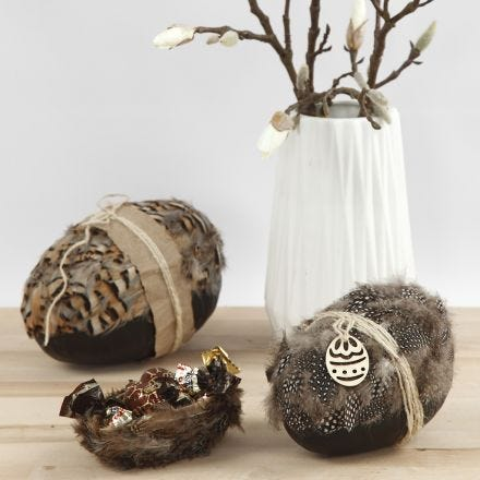 Höyhenillä ja luonnonnarulla koristellut kaksiosaiset munat