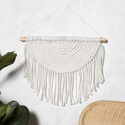 A  macramé wall hanging braided in a semi circle