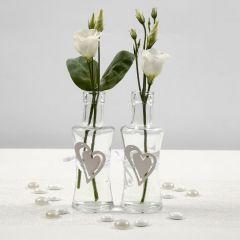 Satiininauhalla ja puisella sydämellä koristellut lasipullot
