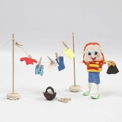 Hahmo Silk Clay:stä ja puinen pyykkinaru, jossa on Silk Clay-vaatteita kuivumassa
