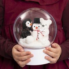 Läpinäkyvä pallo, jonka sisällä on lumiukko, pingviini ja jääkarhu.