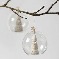 Valkoinen joulukuusi aukollisen lasipallon sisällä