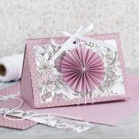 Roosa lahjarasia rosetilla ja kuviopaperilla